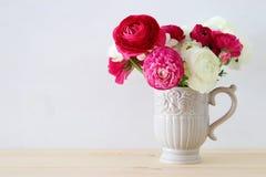 桃红色和白色rosses花束在葡萄酒白色花瓶的 库存照片