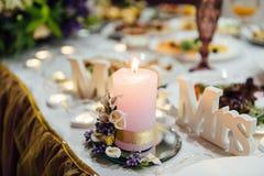 桃红色和白花花束在蜡烛附近的在桌上 库存照片