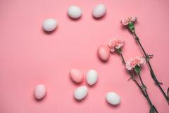 桃红色和白鸡蛋顶视图与花的在桃红色 免版税库存图片