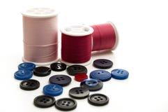 桃红色和红色缝合针线卷与蓝色和黑按钮的 免版税库存图片