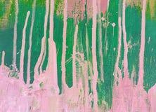 桃红色和绿色油漆明亮的斑点和污点在帆布的 抽象背景 库存照片