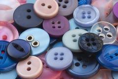 桃红色和蓝色缝合的按钮 库存图片