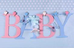 桃红色和蓝色题材婴孩旗布在垂悬从在线的钉上写字 免版税库存照片