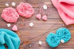 桃红色和薄荷的毛线、snuds、针和编织的心脏缠结  免版税库存图片