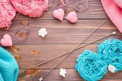 桃红色和薄荷的毛线, snuds,针,编织的心脏缠结  免版税库存照片