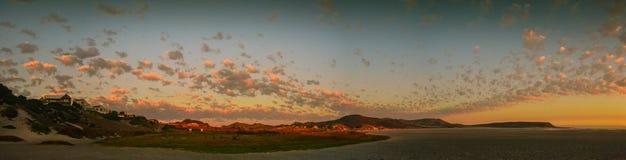 桃红色和金子全景覆盖在海滩在日落 免版税库存图片