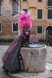 桃红色和黑手工制造服装有爱好者的和华丽被绘的用羽毛装饰的面具的妇女在威尼斯狂欢节 免版税库存图片