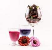 桃红色和紫罗兰的构成充分上色了鸡尾酒,玻璃花和两朵花在白色背景 免版税库存图片