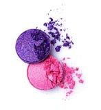 桃红色和紫罗兰击碎了在白色的发光的眼影膏 免版税图库摄影
