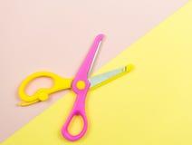 桃红色和黄色五颜六色的剪刀在桃红色和黄色backgro 免版税库存照片