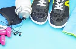 桃红色哑铃、体育瓶、耳机和跑鞋在体育席子 图库摄影