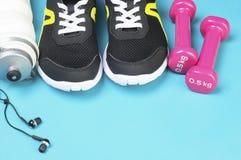 桃红色哑铃、体育瓶、耳机和跑鞋在体育席子 库存图片