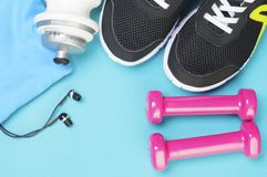 桃红色哑铃、体育瓶、耳机和跑鞋在体育席子 免版税库存图片
