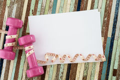 桃红色哑铃和测量的磁带和白纸您的文本的o 免版税库存照片