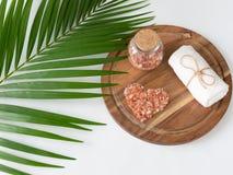 桃红色喜马拉雅盐和毛巾在木板条、monstera和棕榈叶 库存照片