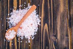 桃红色喜马拉雅盐水晶在棕色木桌上的 免版税库存图片
