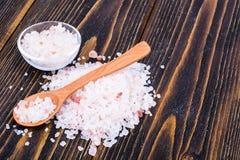 桃红色喜马拉雅盐水晶在棕色木桌上的 库存照片