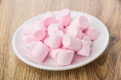 桃红色嚼的蛋白软糖堆在白色茶碟的在桌上 库存图片