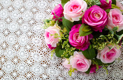 桃红色在白色钩针编织桌布的玫瑰花束 免版税图库摄影