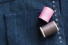 桃红色在蓝色布料的口气缝合针线 免版税库存照片