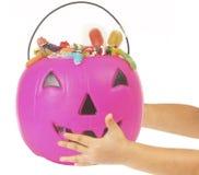 桃红色塑料南瓜用糖果,孩子的手填装了 免版税库存照片