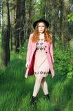 桃红色外套和黑帽会议的画象年轻端庄的妇女 方式 图库摄影