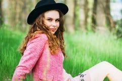 桃红色外套和黑帽会议的画象年轻端庄的妇女 方式 库存照片