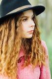 桃红色外套和黑帽会议的画象年轻端庄的妇女 方式 库存图片