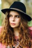 桃红色外套和黑帽会议的画象年轻端庄的妇女 方式 免版税库存图片