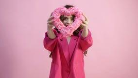 桃红色外套的女孩有心脏的在手中在桃红色背景 概念亲吻妇女的爱人 美丽的诱人的少妇 红色上升了 股票录像
