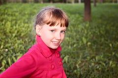 桃红色外套的小逗人喜爱的女孩在autmn公园 免版税图库摄影