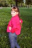 桃红色外套的小逗人喜爱的女孩在autmn公园 免版税库存图片