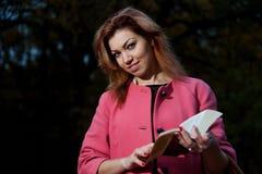桃红色外套的美丽的妇女有书的在公园走 免版税库存图片