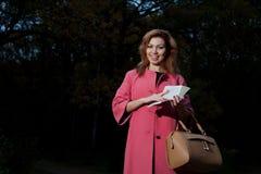 桃红色外套的美丽的妇女有书的在公园走 免版税库存照片