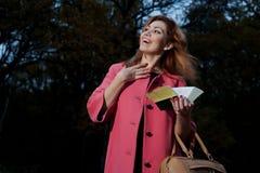 桃红色外套的美丽的妇女有书的在Th走 免版税图库摄影