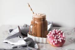 桃红色多福饼用蛋白软糖和热巧克力在玻璃杯子在大理石桌上 库存图片