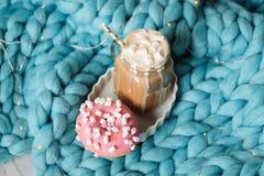 桃红色多福饼用蛋白软糖和热巧克力在玻璃杯子在蓝色美利奴绵羊的编织毯子 在背景的光 免版税库存图片