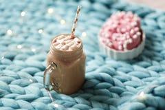 桃红色多福饼用蛋白软糖和热巧克力在玻璃杯子在蓝色美利奴绵羊的编织毯子 在背景的光 库存照片