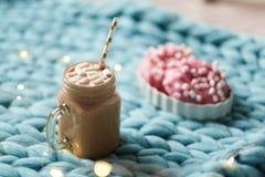 桃红色多福饼用蛋白软糖和热巧克力在玻璃杯子在蓝色美利奴绵羊的编织毯子 在背景的光 库存图片
