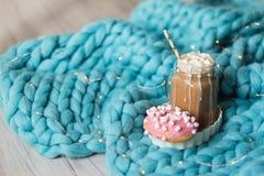桃红色多福饼用蛋白软糖和热巧克力在玻璃杯子在蓝色美利奴绵羊的编织毯子 在背景的光 免版税库存照片