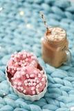 桃红色多福饼用蛋白软糖和热巧克力在玻璃杯子在蓝色美利奴绵羊的编织毯子 在背景的光 免版税图库摄影