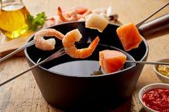 桃红色大虾和新鲜的三文鱼在海鲜涮制菜肴 库存照片