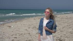 桃红色太阳镜的年轻白肤金发的妇女反对海和天空蔚蓝慢动作 股票视频