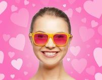 桃红色太阳镜的微笑的十几岁的女孩 免版税库存图片