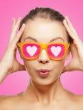 桃红色太阳镜的惊奇的十几岁的女孩 免版税库存照片