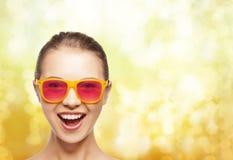 桃红色太阳镜的愉快的十几岁的女孩 免版税图库摄影