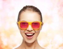 桃红色太阳镜的愉快的十几岁的女孩 免版税库存图片