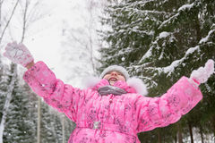桃红色夹克传染性的雪花的小女孩在冬天公园 免版税库存图片