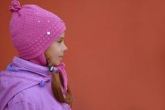 桃红色夹克和帽子的小女孩 免版税库存照片
