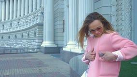 桃红色夹克的俏丽的女孩看智能手机屏幕 股票视频